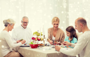 49091127 - family, holidays, generation, christmas and people concept - smiling family having dinner at home
